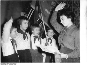Zum 12. Jahrestag der Pionierorganisation erhalten Schüler der Klasse 5b der 12. Oberschule Berlin von ihrer Pionierleiterin einen Wimpel für die Gruppenfahne (1960) (c) Bundesarchiv Bild-183-78706-0002 / Fotograf_in unbekannt