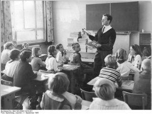 Lehrer verteilt die neuen Schulbücher in der Klasse 5a der 16. Oberschule in Berlin-Mitte (1964) (c) Bundesarchiv Bild-183-O0901-0014-001 / Fotograf Joachim Spremberg